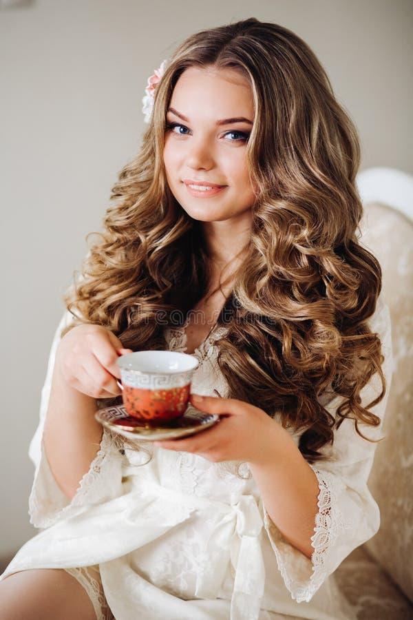 Sexy vrouw in robe het drinken thee in de ochtend Blond golvend haar, mooie make-up, zachte ochtend Meisje die een mok houden stock foto's