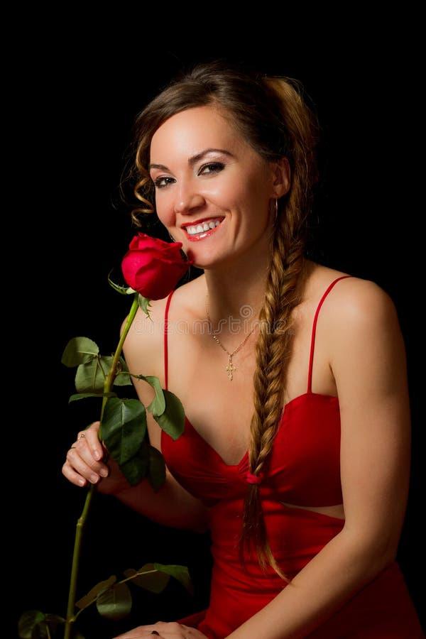 Sexy vrouw in rood met een bloem stock fotografie