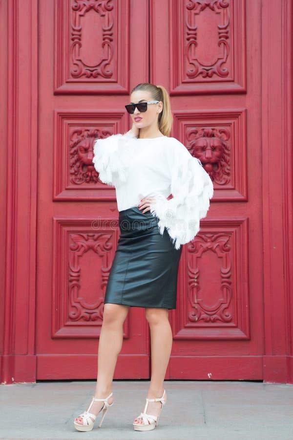Sexy vrouw in zonnebril met lang haar Vrouw in hoge hielschoenen op rode deur in Parijs, Frankrijk Het schoonheidsmeisje met glam stock afbeeldingen