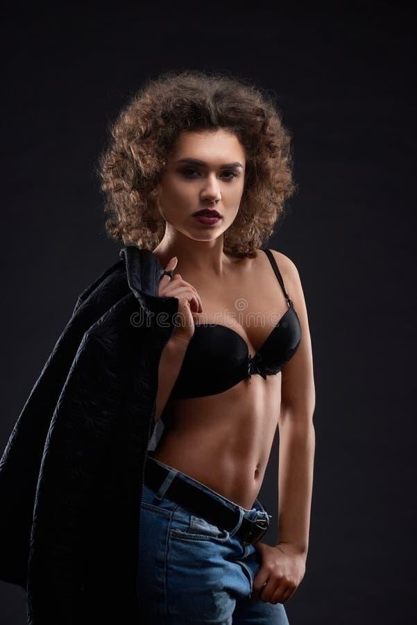 Sexy vrouw in zwarte bustehouder en jeans stock foto