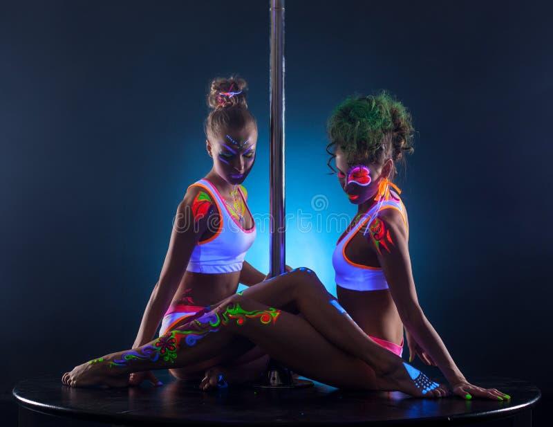 Sexy vrouwelijke dansers die samen dichtbij pool zitten royalty-vrije stock foto's