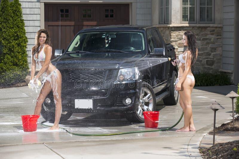 De sexy meisjes wassen een zwarte vrachtwagen in bikinis