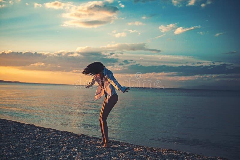 Sexy vrouwendans op Caraïbische overzees in de Bahamas bij zonsondergang Het meisje ontspant op de manierzwempak van het kiezelst royalty-vrije stock afbeelding