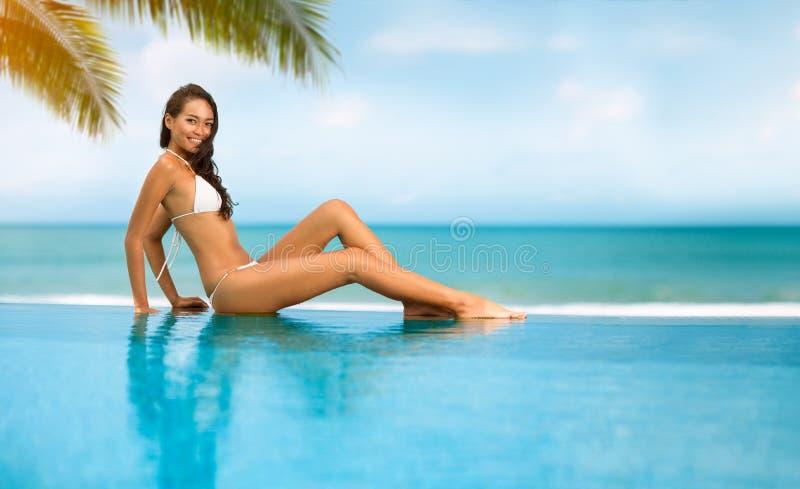 Sexy vrouwenzitting op de rand van de pool royalty-vrije stock foto