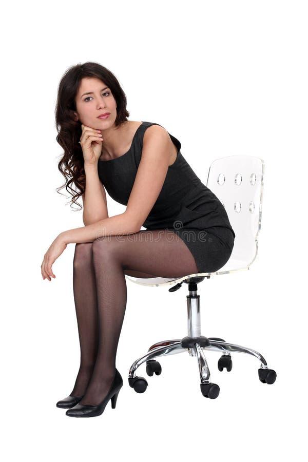 Sexy vrouwenzitting op een stoel stock fotografie