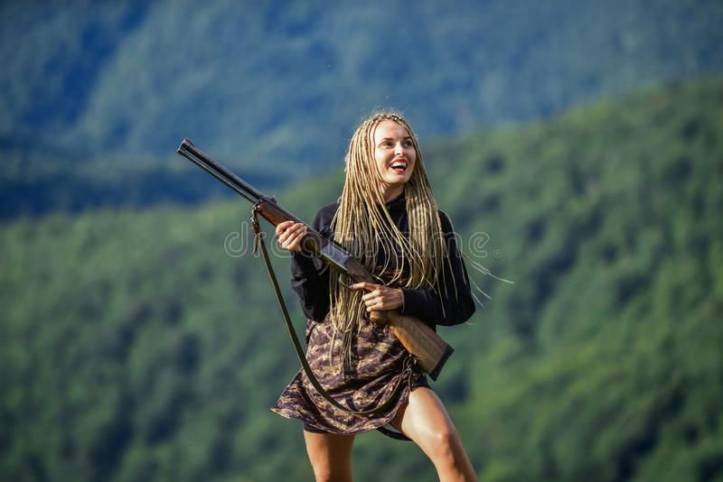 Sexy warrior. She is warrior. Warrior mountains landscape background. Feminist girl. Hunting season. Woman attractive. Long hair pretty face hold rifle for royalty free stock photography