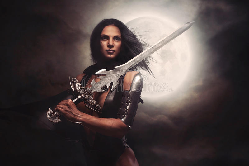 Warrior Woman. With giant fantasy sword and full moon on smoke background royalty free stock images