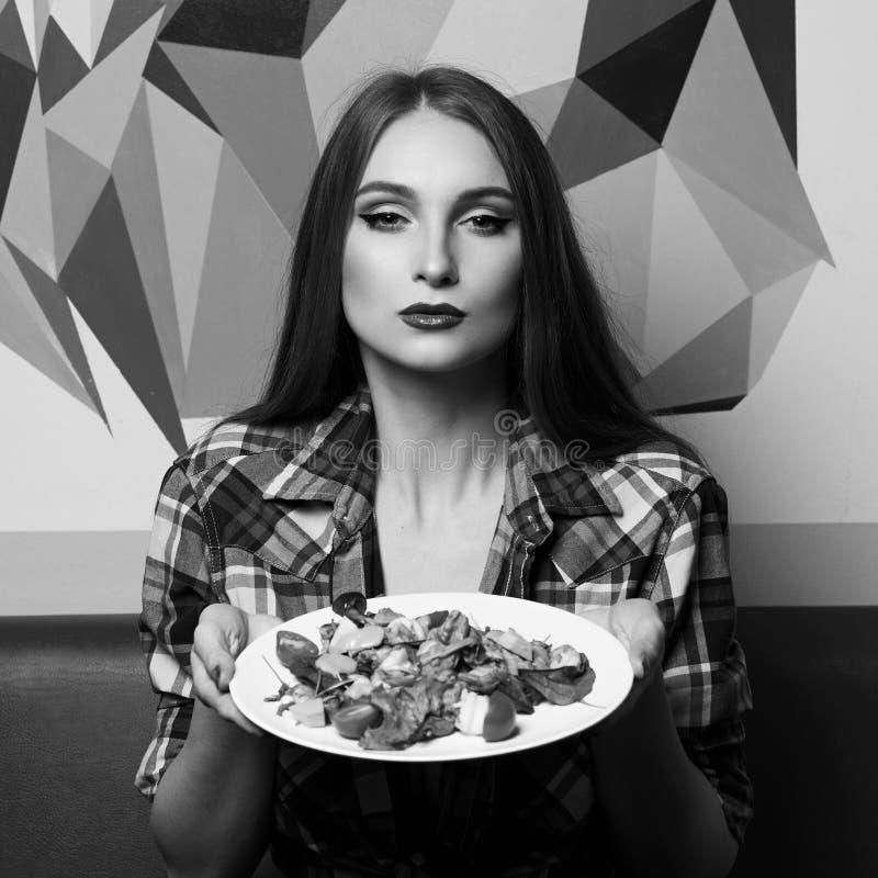 Sexy weibliche vorbildliche zeigende Platte des Salats stockfoto