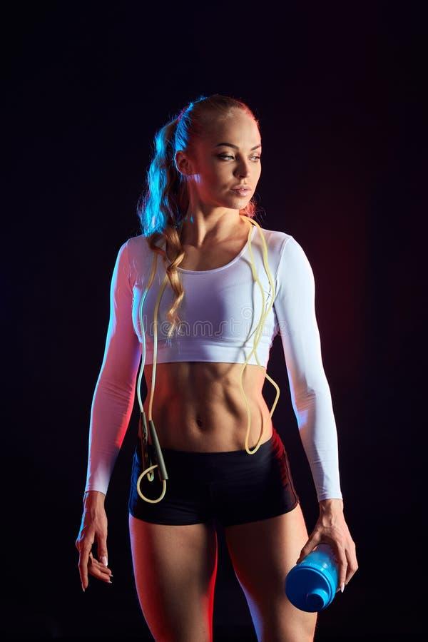 Sexy weiblicher Athlet, der eine Pause nach Training in der Eignungsmitte macht stockfoto
