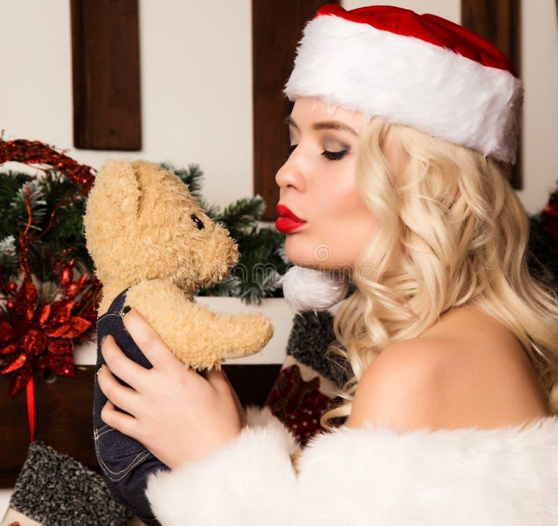 Sexy Weihnachtsmädchen küsst Teddybären Blondine gekleidet als Sankt-Nahaufnahme stockfoto
