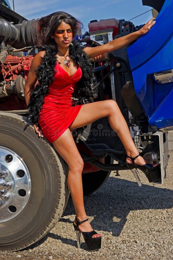 Sexy werkend meisje dat op een semi vrachtwagenband rust stock afbeelding