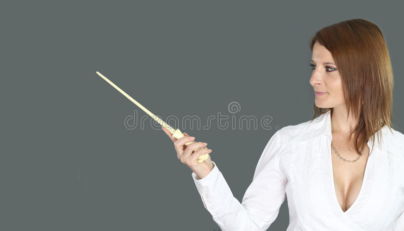 Witch holding a magic wand. Over a gray background royalty free stock images