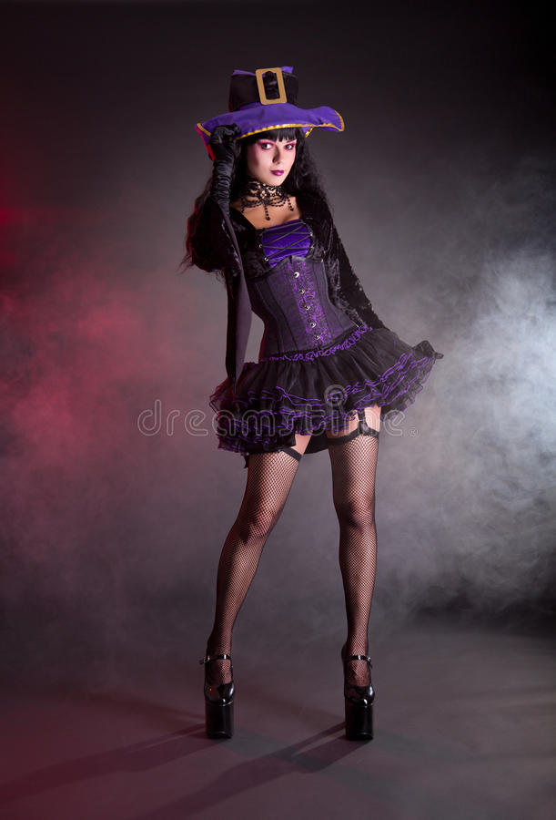 Witch in purple and black gothic Halloween costume. Witch in purple and black gothic fantasy Halloween costume, full length shot royalty free stock image