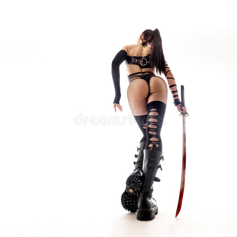 Woman in anime uniform witha a katana sword. ciew from back. Woman in anime uniform witha a katana sword. ciew from back royalty free stock photos