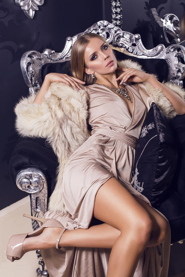Download Woman In Beige Silk Dress Sitting On The Black Armchair Stock Image - Image: 37259611