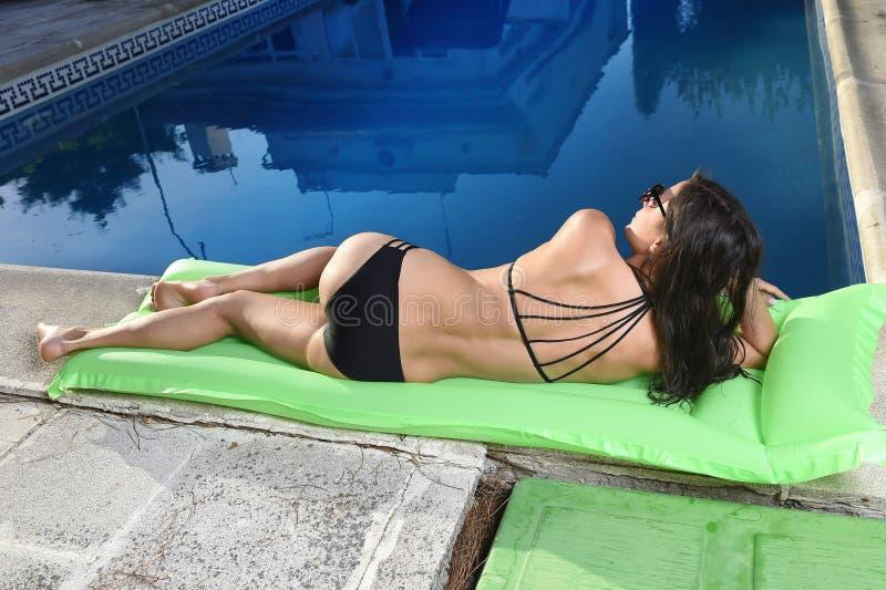 Woman in bikini with beautiful body having suntan relaxing on airbed at swimming pool on sunset. Young woman in bikini and sunglasses with fit beautiful body stock photography