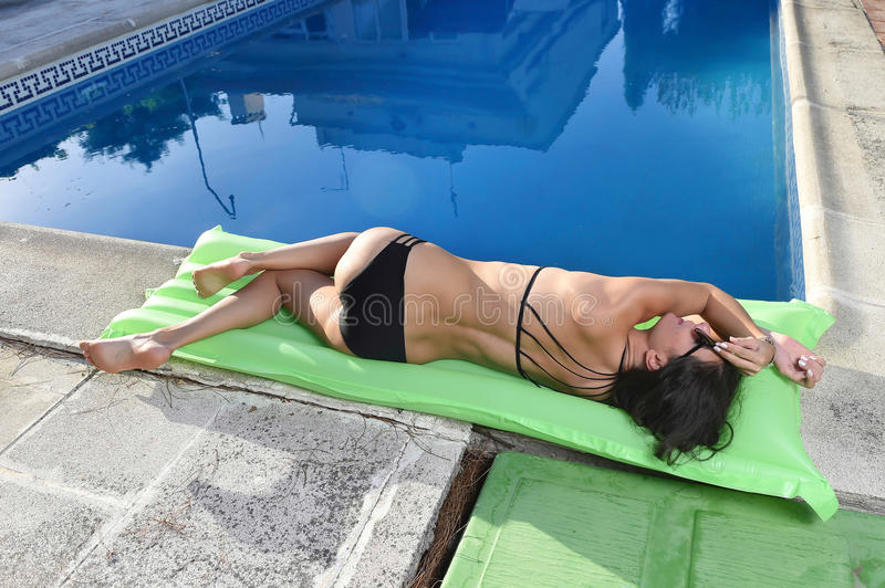 woman in bikini with beautiful body having suntan relaxing on airbed at swimming pool royalty free stock images