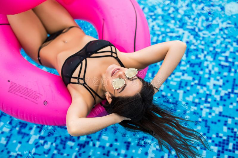 woman in bikini enjoying summer sun and tanning during holidays in pool with cocktail. Top view. Woman in swimming pool. stock photos