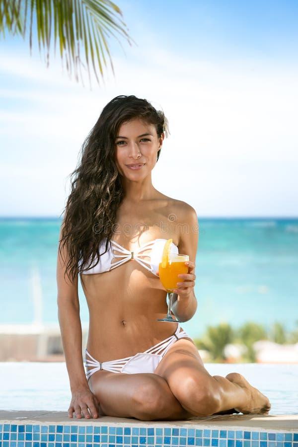 woman in a bikini sitting on the edge of the pool stock photo