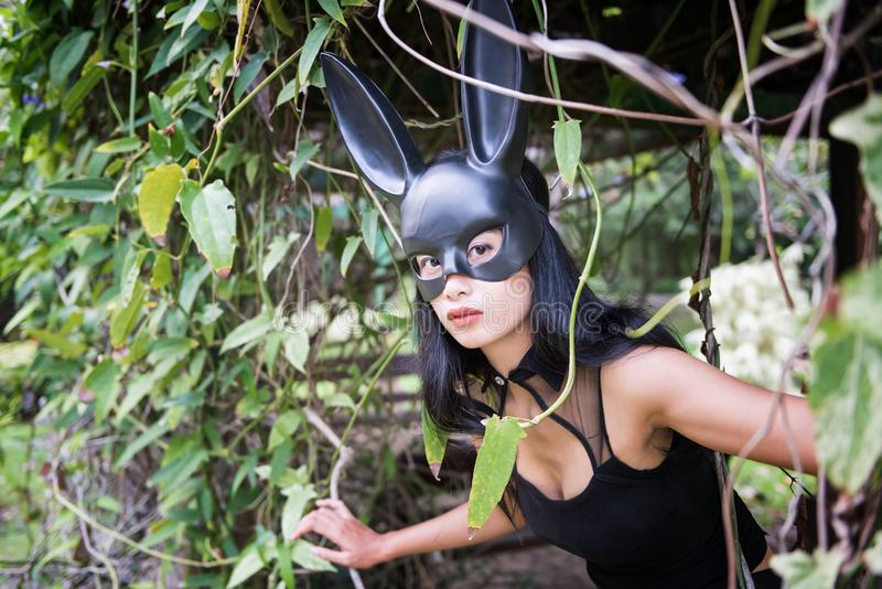 woman with black dress and bunny ear stock photo