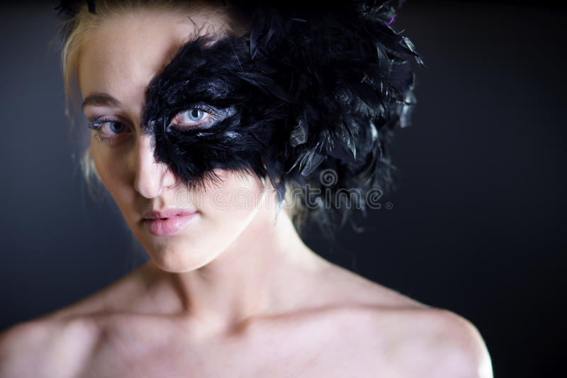 Woman with black feather half mask. Portrait of woman with black feather half mask for Venice desire concept royalty free stock image