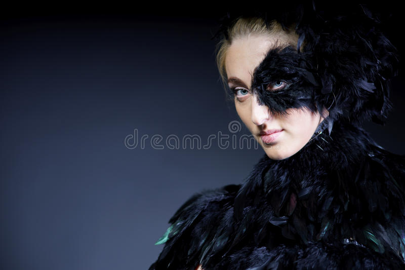 Woman with black feather half mask. Portrait of woman with black feather half mask for Venice desire concept royalty free stock photo