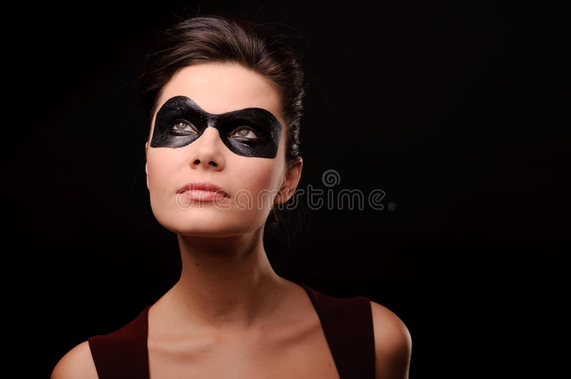 Woman with black party mask on face. Portrait of woman with black party mask on face, isolated on black royalty free stock images
