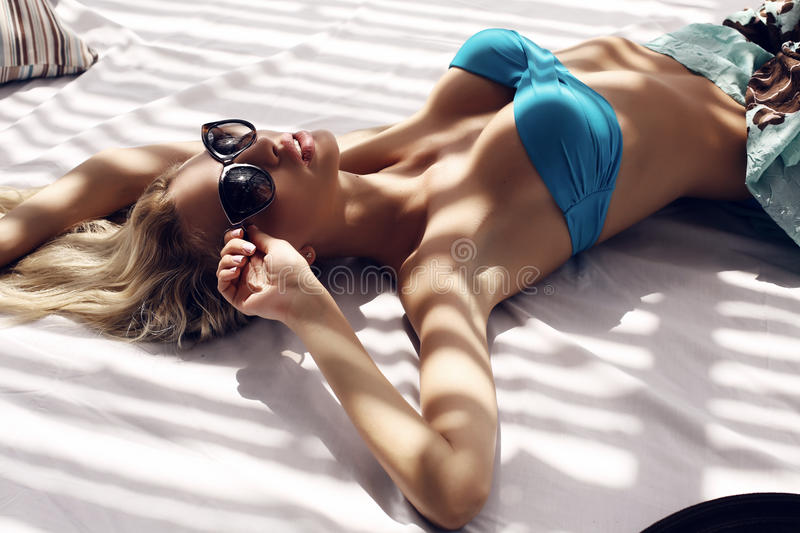 Woman with blond hair in bikini and sunglasses relaxing on beach. Fashion photo of beautiful woman with blond wet hair in blue bikini and sunglasses relaxing on stock photography