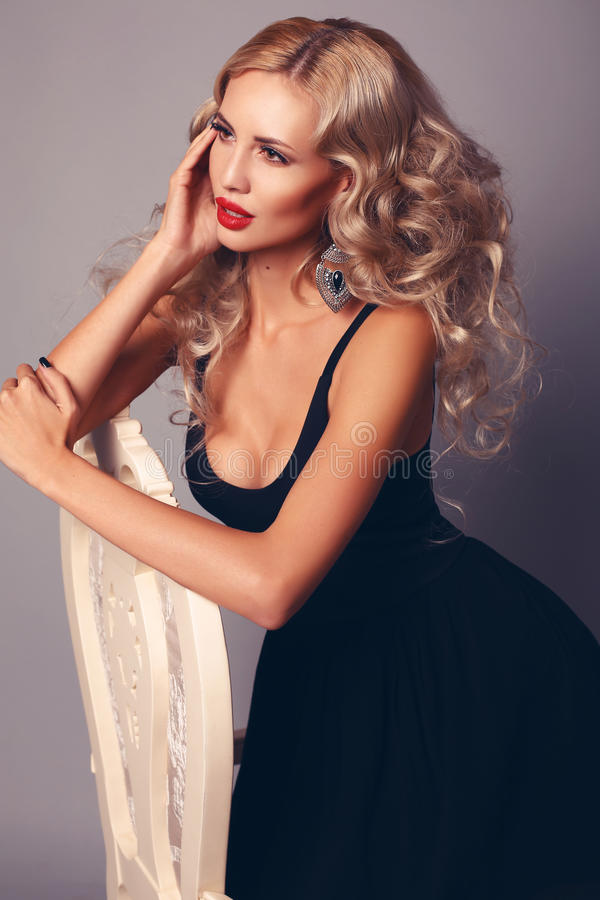 woman with blond hair in elegant black dress posing at studio royalty free stock photos