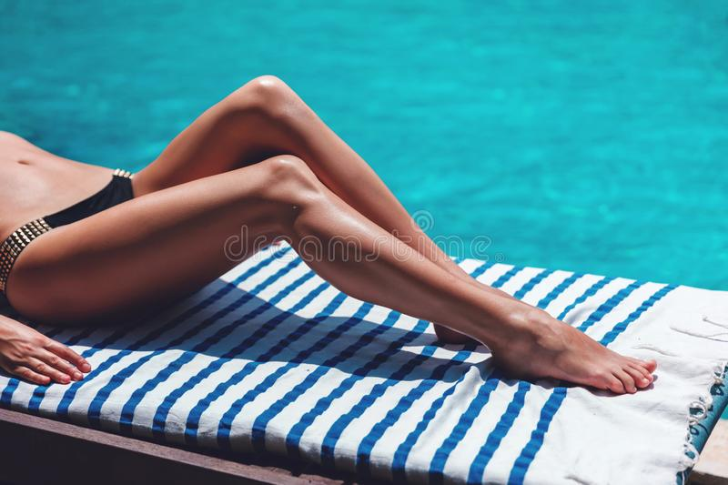 Sexy woman body legs tan. Summer leisure. Blue background. Body skin protection sun cream. Travel lifestyle. royalty free stock photos