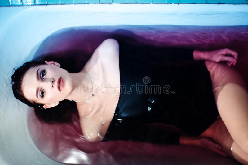 woman in the bodysuit in the bath. Bright light and colored water. Bare Shoulders stock image