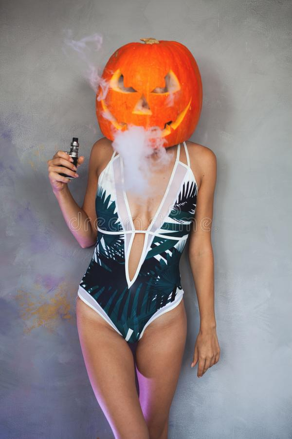 Woman with carved pumpkin on her head for Halloween. Unusual woman with carved pumpkin on her head and wearing swimsuit for Halloween party. She is smoking Vapor stock images