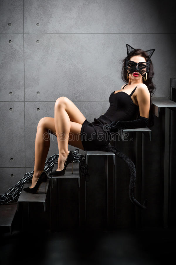 Woman in catwoman suit lying on stairs. At backyard of building royalty free stock photos