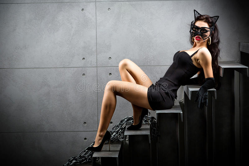 Woman in catwoman suit lying on stairs. At backyard of building stock photography