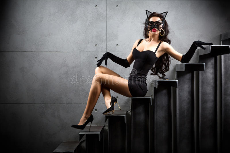 Woman in catwoman suit lying on stairs. At backyard of building stock image