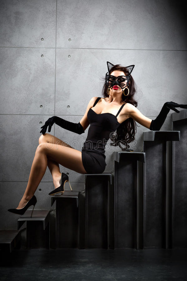 Woman in catwoman suit lying on stairs. At backyard of building royalty free stock images