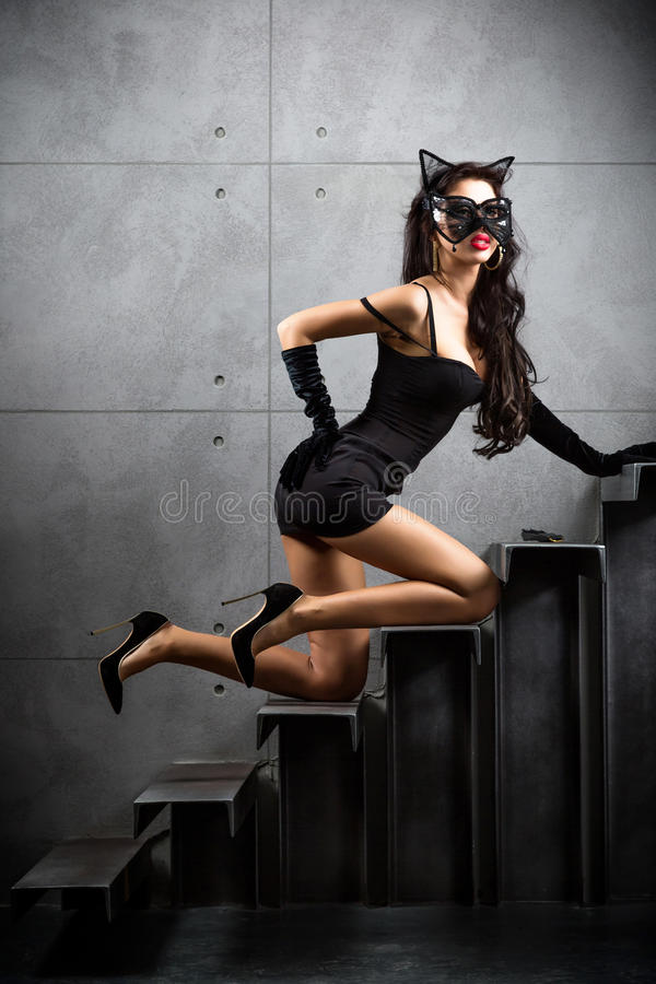 Woman in catwoman suit lying on stairs. At backyard of building stock images