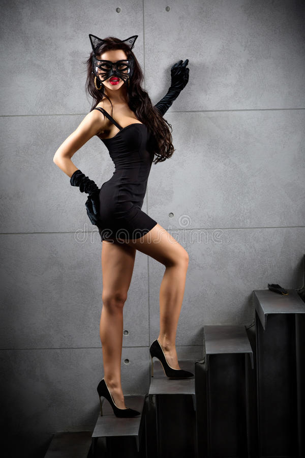 Woman in catwoman suit staying on stairs. At backyard of building royalty free stock photos