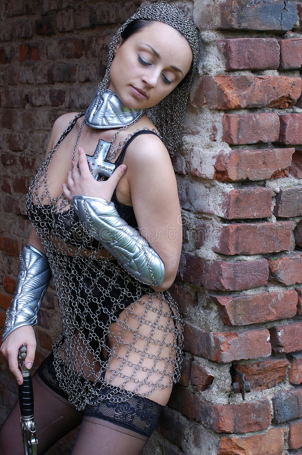 Woman in chain mail. Portrait of woman wearing chain mail over underwear, holding sword stock photos