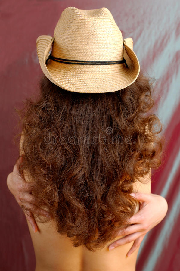 Woman in a Cowboy Hat. Woman with long brown hair in cowboy hat posing with her back to the camera royalty free stock photography