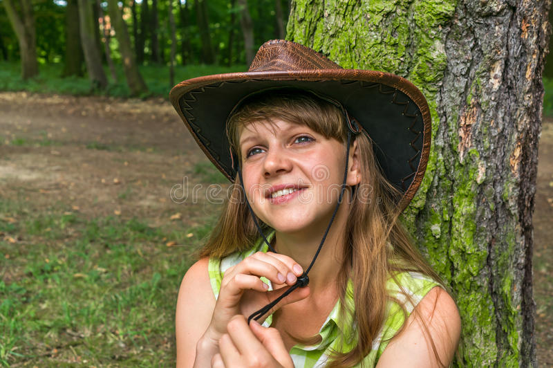 woman with cowboy hat in park stock photo