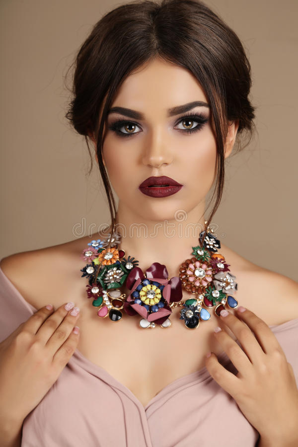 Woman with dark hair and bright makeup, with necklace. Fashion studio photo of gorgeous woman with dark hair and bright makeup, with luxurious necklace royalty free stock photo