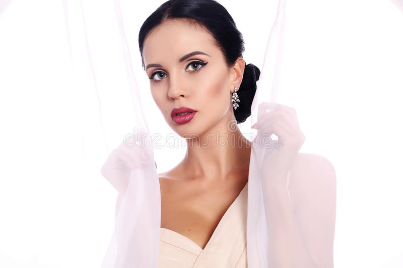 Woman with dark hair with evening makeup and bijou. Fashion interior photo of beautiful woman with dark hair with evening makeup and bijou royalty free stock image