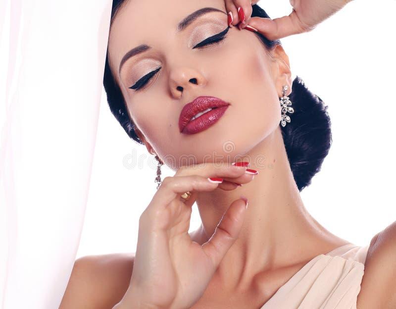 Woman with dark hair with evening makeup and bijou. Fashion interior photo of beautiful woman with dark hair with evening makeup and bijou stock photos