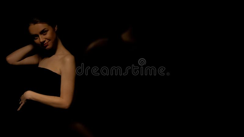 Sexy woman in dress posing for camera, isolated on black background, seduction. Stock photo stock photos