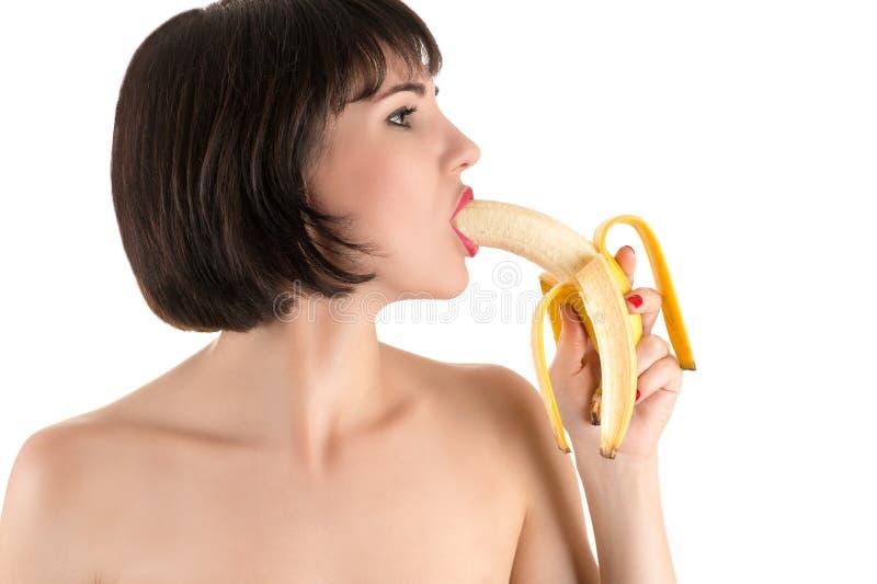 Woman eating banana. Isolated on white background royalty free stock photos