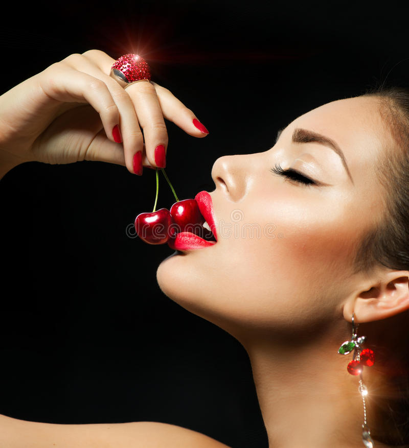 Woman Eating Cherry. Sensual red Lips with Cherries royalty free stock photo