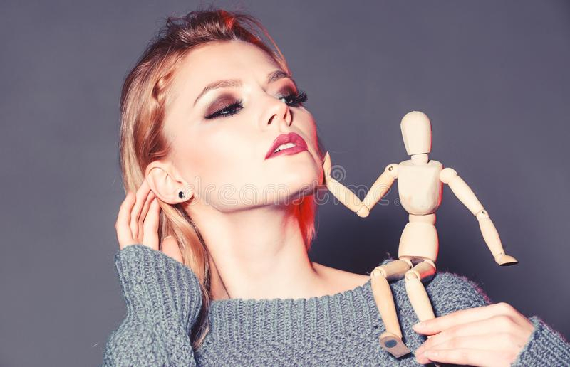 Sexy woman with fashion makeup. wooden figure on shoulder of girl. natural beauty. artificial fashion. vogue concept. Professional visage. womens power. woman stock image