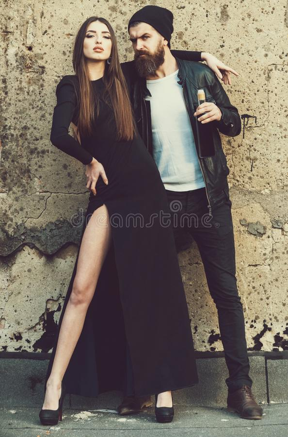 woman in fashionable, black dress hugging handsome, bearded man stock images