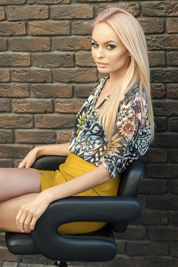 woman in fashionable clothes sit in armchair, fashion. Woman with long blond hair, makeup face, beauty. Fashion stock images